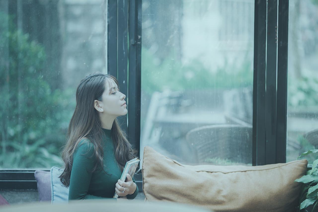 カフェで窓の外を見つめる女性